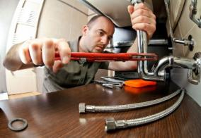 Plumber in Antelope CA tightens sink drain with a pipe wrench